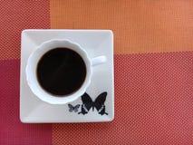 Kaffe ?verst av ett tefat med fj?rilsdesign fotografering för bildbyråer
