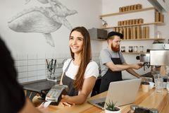 Kaffeaffärsidé - härlig kvinnlig barista som ger betalningservice för kund med kreditkorten och att le arkivbild