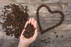 Kaffeböna i hand och hjärta en trätabell Härlig bakgrund Royaltyfria Bilder
