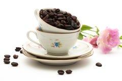Kaffeböna i kopp Arkivfoto