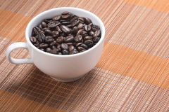 Kaffeböna i kopp Arkivbild