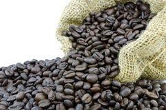 Kaffeböna i säckvävpåse med vit isolatbakgrund Royaltyfria Bilder