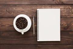 Kaffeböna i tom sida för kopp och för bok på den wood tabellen royaltyfria bilder