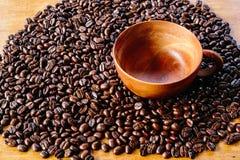 Kaffeböna och träkopp Arkivbild