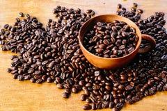 Kaffeböna och träkopp Arkivfoton