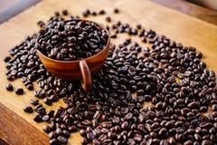Kaffeböna och träkopp Royaltyfria Bilder
