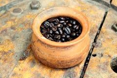 Kaffebönan övermättar in krukan på bakgrundsträ Royaltyfria Foton