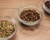 Kaffebönor av medelstek i en glass bunke som omges av gräsplan Arkivbild
