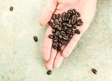 Kaffebönor bar in en hand Arkivbild