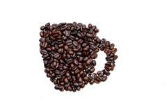 Kaffebönor formade in i en kopp Arkivfoto