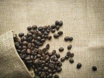 Kaffebönor från en påse för tappningbakgrundskaffe royaltyfria foton