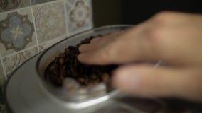 Kaffebönor hällde in i en kaffemaskin arkivfilmer