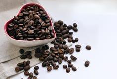 Kaffebönor hällde in i en liten kopp i form av en hjärta arkivbild