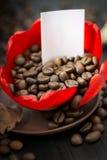 Kaffebönor i den röda blomman för knopp, papper med ditt häfte Arkivfoton