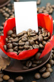 Kaffebönor i den röda blomman för knopp, papper med ditt häfte Arkivfoto
