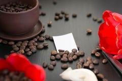 Kaffebönor i den röda blomman för knopp, papper med ditt häfte Royaltyfri Fotografi
