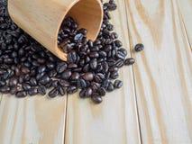 Kaffebönor i den wood koppen på träbräde Arkivbilder
