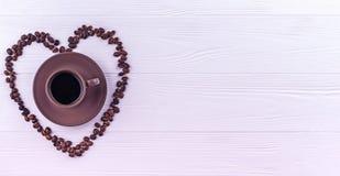 Kaffebönor i en form av en hjärta med en kopp kaffe på en vit träbakgrund Royaltyfria Bilder