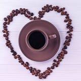Kaffebönor i en form av en hjärta med en kopp kaffe på en vit träbakgrund Royaltyfri Fotografi