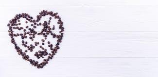 Kaffebönor i en form av en hjärta på en vit träbackgroun Royaltyfri Foto