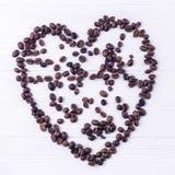 Kaffebönor i en form av en hjärta på en vit träbakgrund Arkivbild