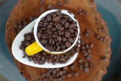 Kaffebönor i en gul kopp på det vita keramiska magasinet på en stubbe Royaltyfri Foto
