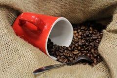 Kaffebönor i en jutepåse, en tesked och ett rött kaffe rånar royaltyfria foton