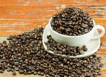 Kaffebönor i en kopp och spill ut ur en kopp Arkivbilder