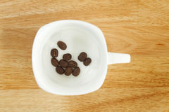 Kaffebönor i en kupa Arkivbild