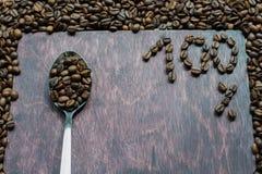Kaffebönor i en sked arkivfoto