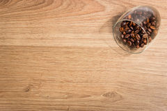 Kaffebönor i ett exponeringsglas på en träbrädebakgrund Arkivfoto