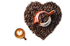 Kaffebönor i formen av en stor hjärta med rånar Arkivfoton