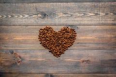 Kaffebönor i hjärta formar på mörk träcopyspace för bästa sikt för tabell klart bruk för bakgrundskaffe Arkivfoton