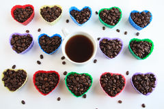 Kaffebönor i hjärtaform gjuter med kaffekoppen i mitt Royaltyfria Bilder