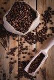 Kaffebönor i jute plundrar och skopan på träbakgrund, bästa sikt arkivfoton