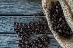 Kaffebönor i jute plundrar på träbakgrund royaltyfria foton