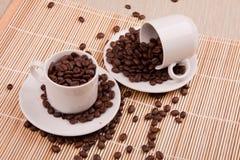 kaffebönor i kaffekoppar Arkivfoto