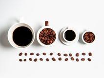 Kaffebönor i koppar som isoleras på vit Arkivfoton