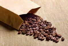 Kaffebönor i kraft papper på tabellen Royaltyfri Fotografi