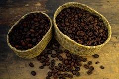 Kaffebönor i massa på den wood tabellen och ett mjukt ljus Arkivfoto