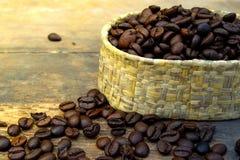 Kaffebönor i massa på den wood tabellen och ett mjukt ljus Royaltyfria Bilder