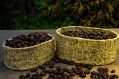Kaffebönor i massa på den wood tabellen och ett mjukt ljus Royaltyfri Foto