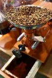 Kaffebönor i molar med kvarnstenar Arkivfoton