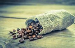 Kaffebönor i säckvävpåsen Arkivbild