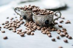 Kaffebönor i silvertappningkoppar på träbakgrund Royaltyfri Fotografi