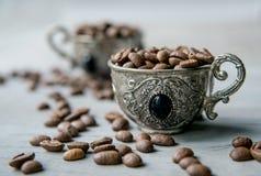 Kaffebönor i silvertappningkoppar på träbakgrund Royaltyfria Bilder