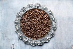 Kaffebönor i silvertappningplatta på träbakgrund Arkivfoto