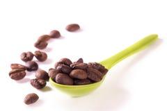 Kaffebönor i skeden Arkivbilder