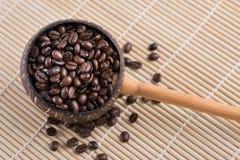 Kaffebönor i skopa arkivbild