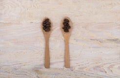 Kaffebönor i träskedar Arkivfoto